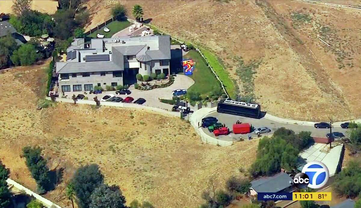 This image from aerial video provided by KABC-TV shows the home of entertainer Chris Brown with a police vehicle outside, in the Tarzana area of Los Angeles Tuesday, Aug. 30, 32016. Authorities waited for a search warrant outside Brown's Los Angeles home Tuesday after a getting a woman's call for help, officials said. Inside, the entertainer, who has a history of legal problems, posted videos to social media declaring his innocence. (KABC-TV via AP) MANDATORY CREDIT TV OUT