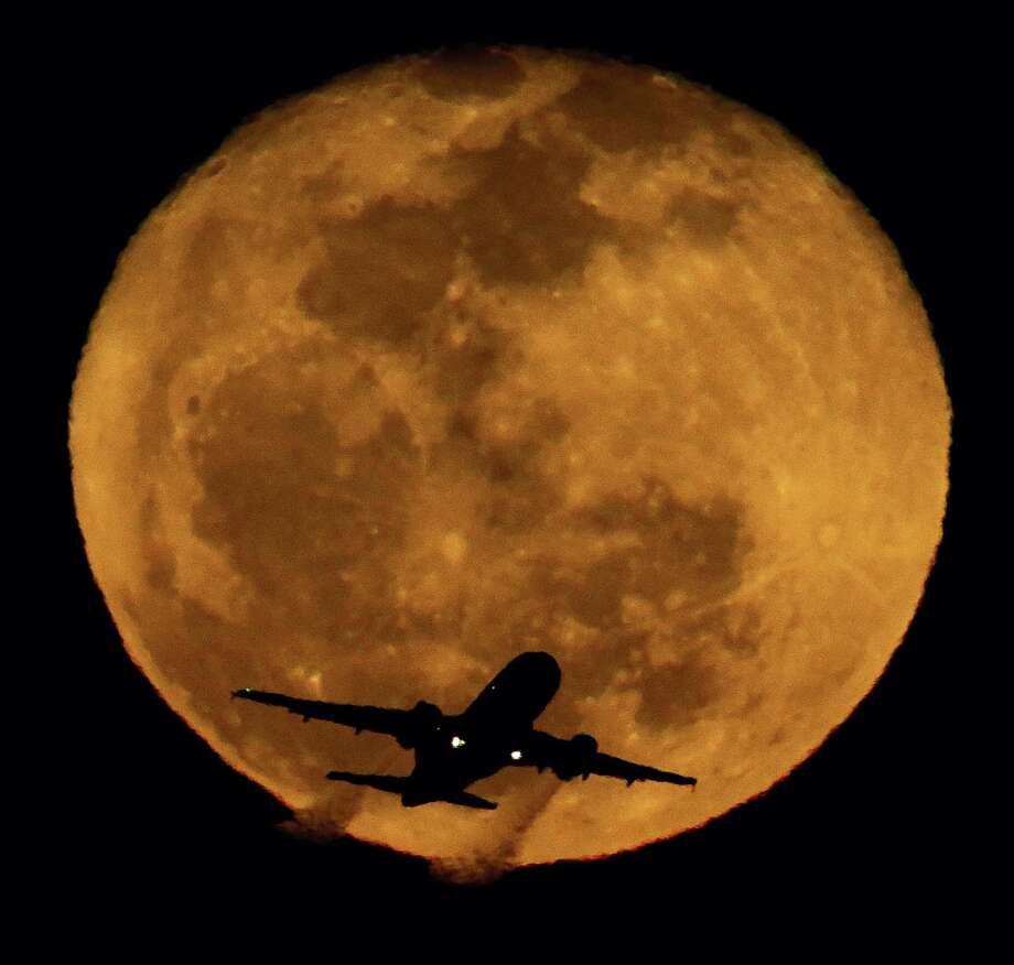 In this Feb. 26, 2013 photo, a waning moon rises in the distance as a passenger jet takes off at Phoenix's Sky Harbor Airport. A handful of U.S. pilots each year fail random sobriety tests. Those who fail can fly again if they prove rehabilitation. Photo: AP Photo/Charlie Riedel, File  / AP2013