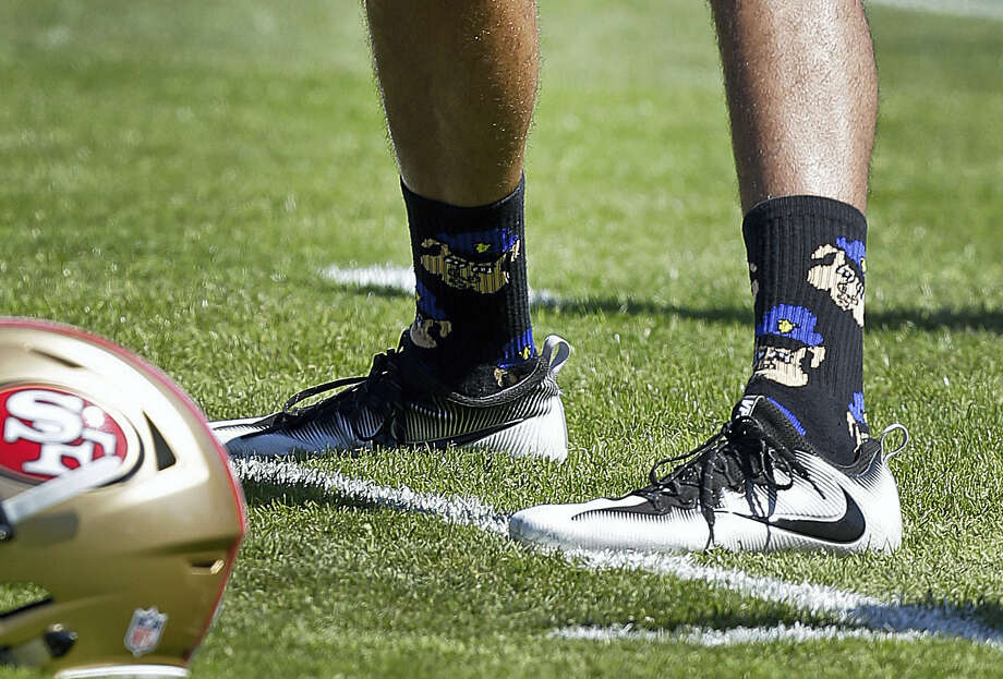 San Francisco 49ers quarterback Colin Kaepernick wears socks depicting police officers as pigs during training camp on Aug. 10 at Kezar Stadium in San Francisco. Photo: The Associated Press File Photo  / Copyright 2016 The Associated Press. All rights reserved. This material may not be published, broadcast, rewritten or redistribu