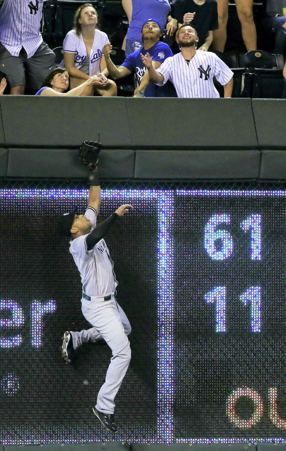Yankees right fielder Aaron Hicks climbs the outfield wall on Alcides Escobar's home run in the seventh inning on Monday.