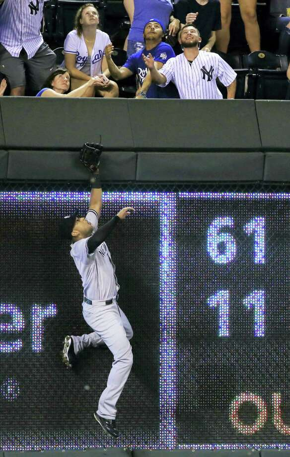 Yankees right fielder Aaron Hicks climbs the outfield wall on Alcides Escobar's home run in the seventh inning on Monday. Photo: Orlin Wagner — The Associated Press  / Copyright 2016 The Associated Press. All rights reserved.