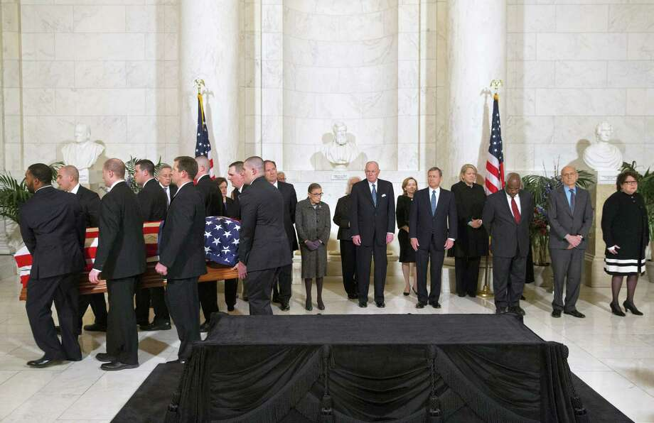 The casket of late Supreme Court Justice Antonin Scalia is carried into the Great Hall of the Supreme Court for a private ceremony in Washington, Friday Feb. 19, 2016, past Supreme Court Justices from back left Counselor to the Chief Justice Jeffrey Minear, and Supreme Court Justices Elena Kagan, Samuel Anthony Alito, Jr., Ruth Bader Ginsburg, Anthony Kennedy, Chief Justice John Roberts, Jr., Clarence Thomas, Stephen Breyer, and Sonia Sotomayor. (AP Photo/Jacquelyn Martin, Pool) Photo: AP / AP Pool