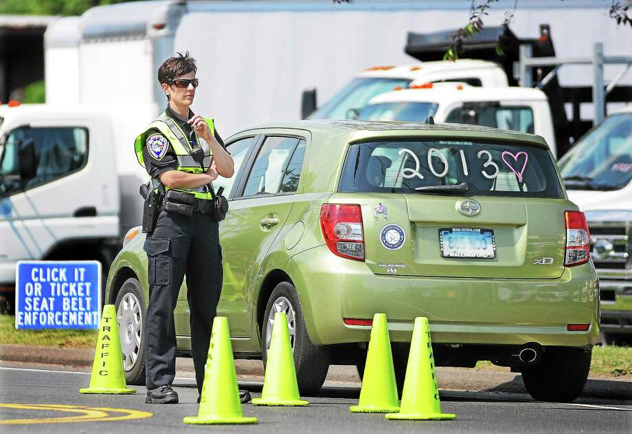 A police officer checks motorists driving without seatbelts during a recent Click It or Ticket enforcement campaign. Photo: File Photo  / TheMiddletownPress