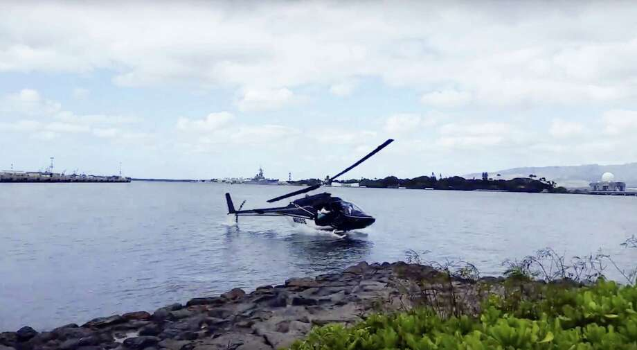 In this image taken from video provided by Shawn Winrich, a helicopter crashes near Parl Harbor, Hawaii on Thursday, Feb. 18, 2016. The private helicopter with five people aboard crashed and sunk into the water, leaving a teenage passenger in critical condition. Photo: Shawn Winrich Via The AP   / Shawn Winrich