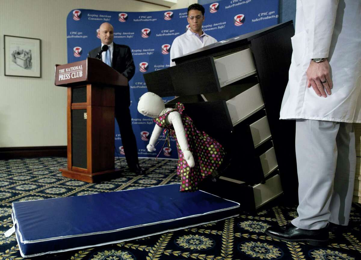 Consumer Product Safety Commission (CPSC) Chairman Elliot Kaye, left, watches a demonstration of how an Ikea dresser can tip and fall on a child during a news conference at the National Press Club in Washington on June 28, 2016. Ikea is recalling 29 million chests and dressers after six children were killed when the furniture toppled over and fell on them.