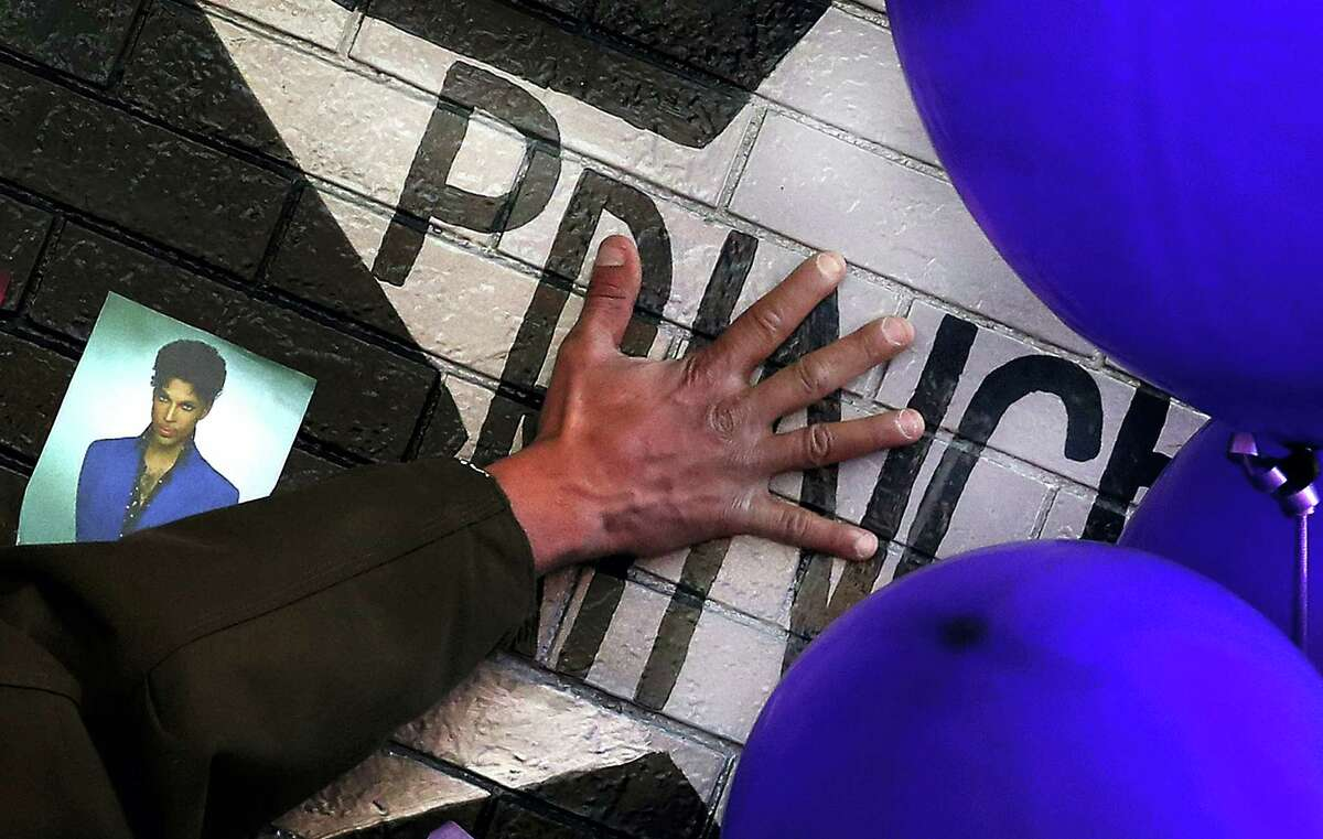 A mourner and fan touches the star for Prince on a wall at First Avenue where the singer often performed, Saturday, April 23, 2016, in Minneapolis. The pop superstar died Thursday, April 21, 2016 at the age of 57.
