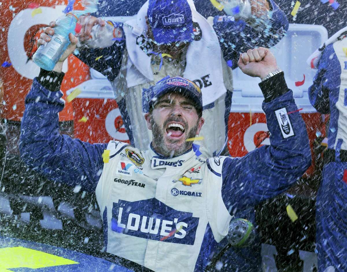 Jimmie Johnson celebrates after winning the NASCAR Sprint Cup Series auto race at Martinsville Speedway in Martinsville, Va. on Oct. 30, 2016.