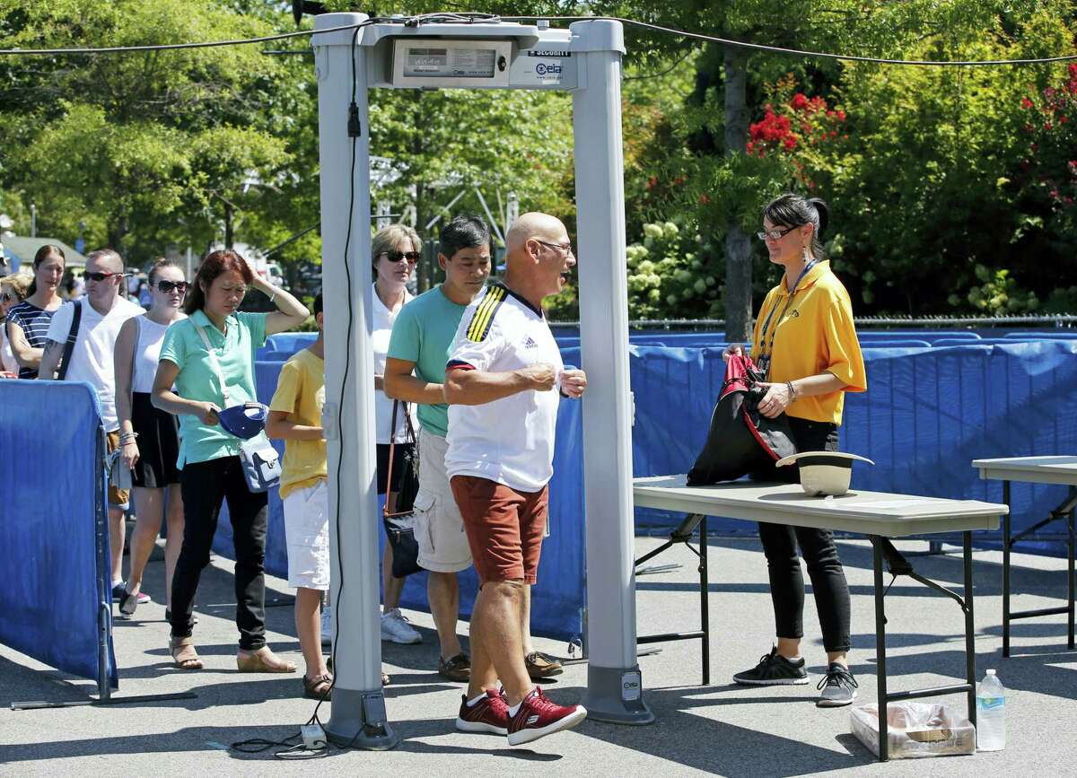 Spectators go through a metal detector while entering the Billie Jean King National Tennis Center, site of the U.S. Open Tennis Tournament in New York.