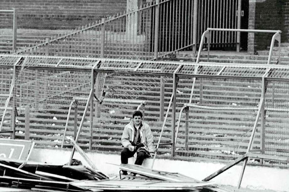 """In this 1989 file photo, a lone soccer supporter sits by the damaged fencing at Hillsborough Stadium, in Sheffield, England. The 96 Liverpool soccer fans who died in the Hillsborough Stadium disaster were """"unlawfully killed"""" because of errors by the police, a jury concluded on Tuesday. Photo: The Associated Press File Photo  / AP"""