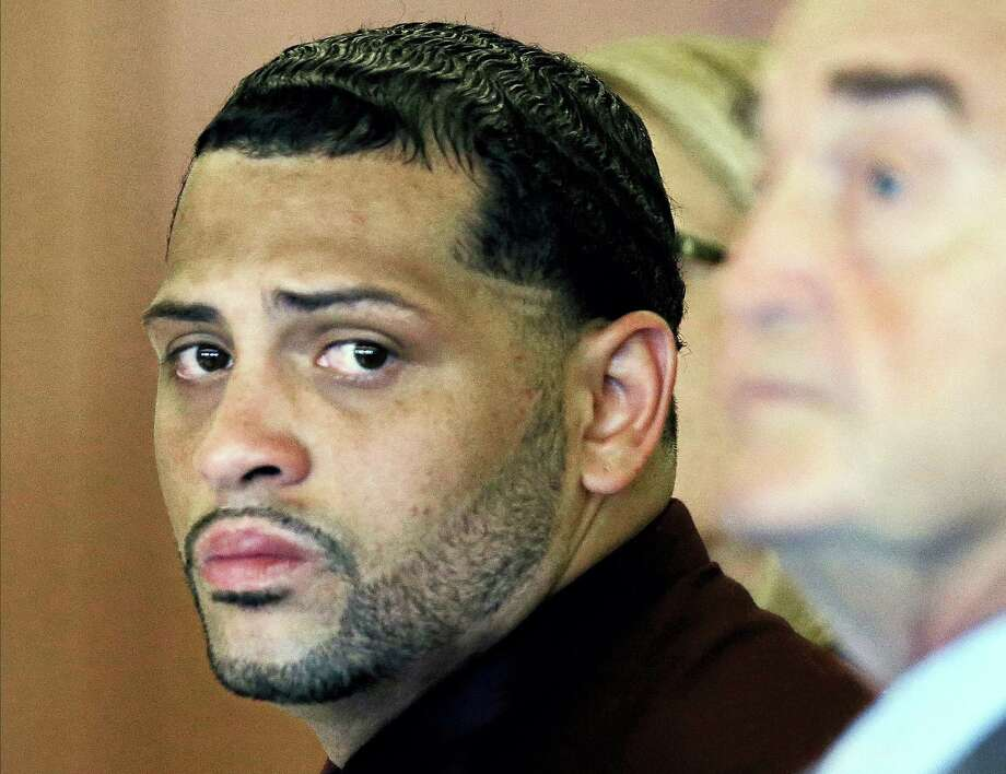 In this 2015 file photo, Carlos Ortiz, co-defendant of former New England Patriots player Aaron Hernandez, sits with his defense attorney John Connors. Photo: The Associated Press File Photo  / Copyright 2016 The Associated Press. All rights reserved. This material may not be published, broadcast, rewritten or redistribu