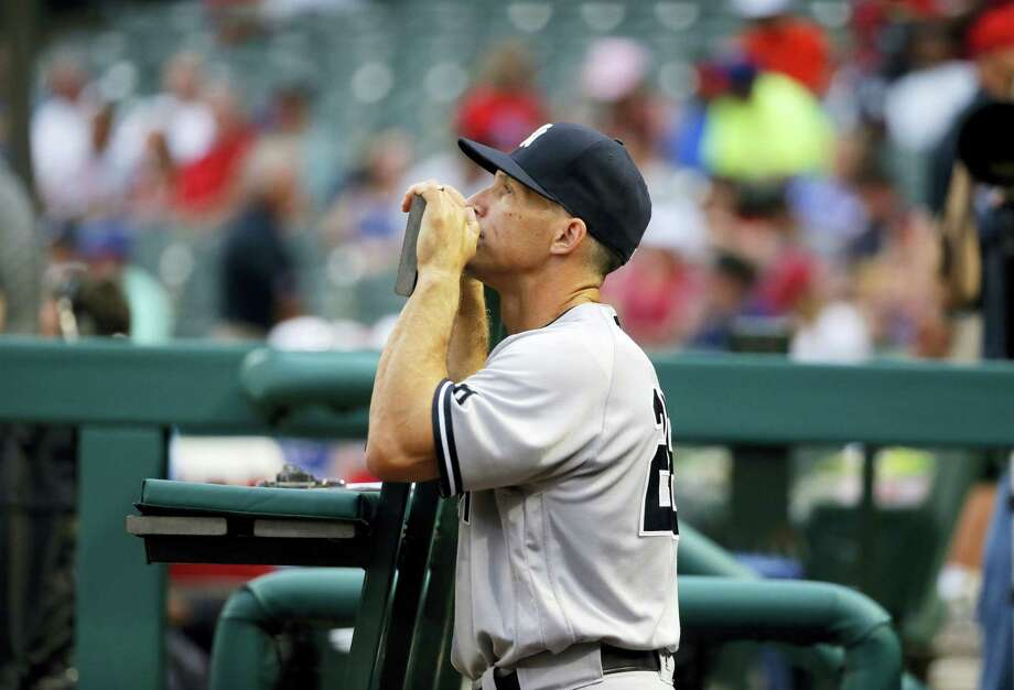 Yankees manager Joe Girardi stands in the dugout during Tuesday's game against the Rangers. Photo: The Associated Press  / AP