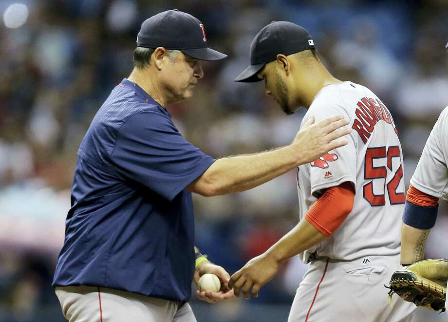 Red Sox manager John Farrell, left, takes the ball from starting pitcher Eduardo Rodriguez during the third inning on Monday. Photo: Chris O'Meara — The Associated Press  / Copyright 2016 The Associated Press. All rights reserved. This material may not be published, broadcast, rewritten or redistribu