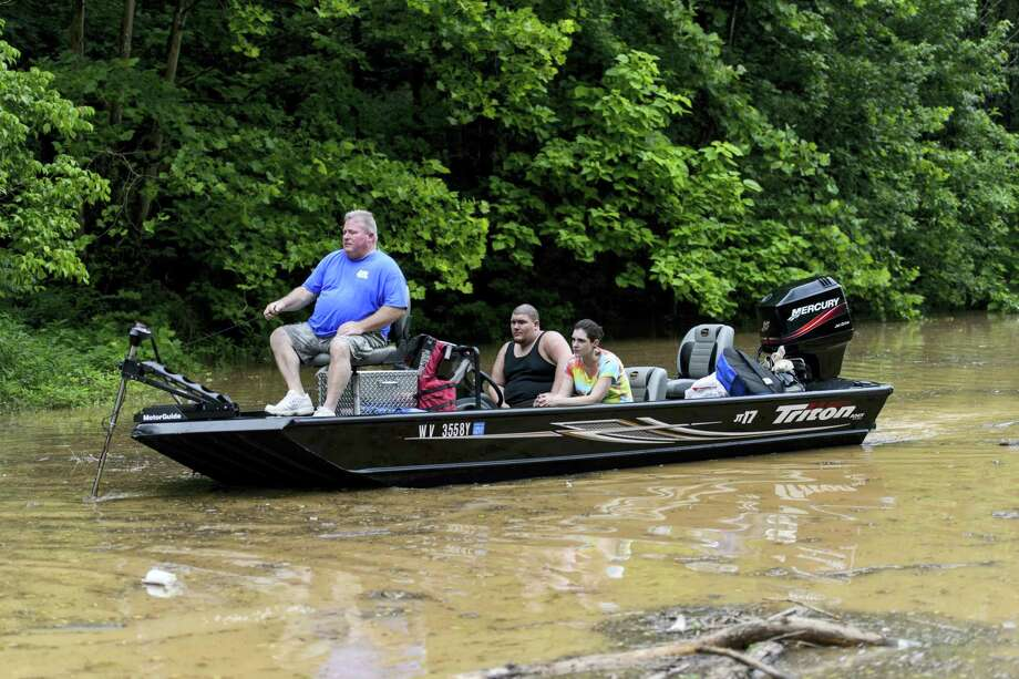 Doug May steers his boat across Frame Road, which was partially flooded, after rescuing Shawn Berry and Darcy Cochran from a parking lot in Elkview, W.Va., Friday, June 24, 2016. Photo: Sam Owens/Charleston Gazette-Mail Via AP   / Charleston Gazette-Mail