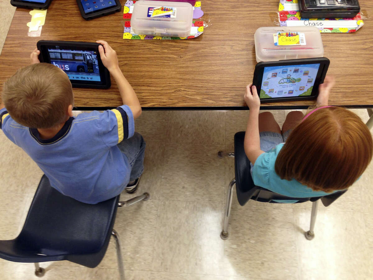 Two students do activities on iPads in a classroom.
