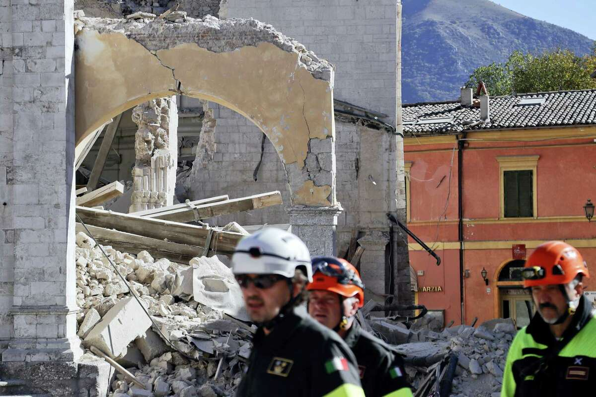 Italian firefighters gather near the collapsed Cathedral of St. Benedict in Norcia, central Italy on Oct. 31, 2016. In the town of Norcia, closest to the epicenter, firefighters were preparing to take people back to their homes early Monday to retrieve belongings.