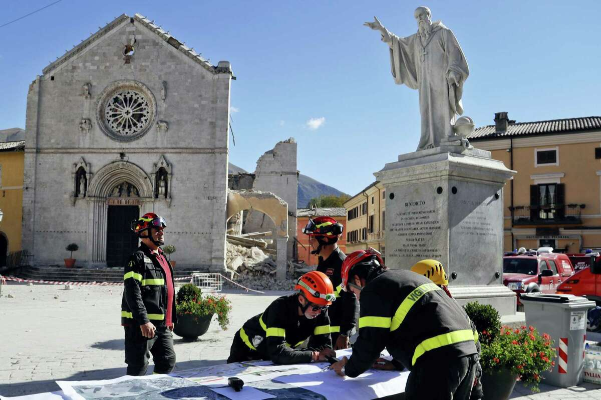 Italian firefighters gather near the collapsed Cathedral of St. Benedict in Norcia, central Italy, Monday, Oct. 31, 2016. In the town of Norcia, closest to the epicenter, firefighters were preparing to take people back to their homes early Monday to retrieve belongings. (AP Photo/Gregorio Borgia)