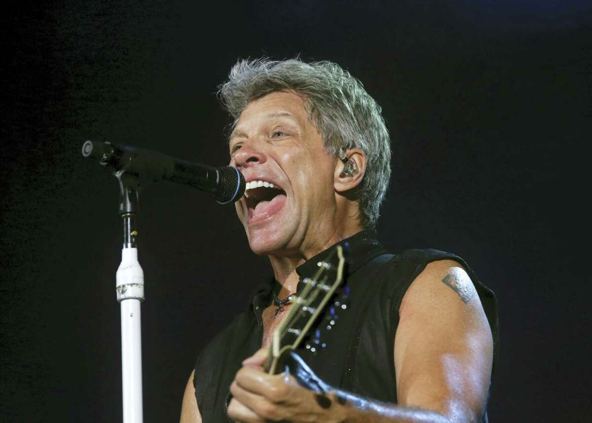 """AP Photo/Tatan Syuflana, File In this Sept. 11, 2015, file photo, Bon Jovi's lead singer Jon Bon Jovi performs during their """"Bon Jovi Live!"""" concert at Gelora Bung Karno Stadium in Jakarta, Indonesia, on their Asia tour. A New Jersey woman battling lung cancer has received an unforgettable surprise from one of the state's most famous rockers, Bon Jovi. Rosie Skripkunis says her mother, Carol Cesario, is a lifelong fan of Bon Jovi and has always wanted to meet him. Last month, Skripkunis shared a sign on social media asking the singer to visit her mother. Bon Jovi surprised Cesario at his Toms River restaurant on Saturday with an autographed guitar and a kiss."""