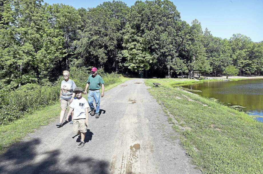 Gauge Trusdell, 7, of Stratford walks with his grandparents, Kathy and Walt Trusdell of Hamden, through Wharton Brook State Park in Wallingford Aug. 22. Photo: Arnold Gold-New Haven Register
