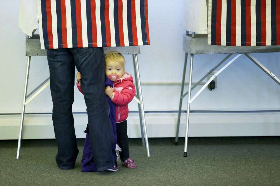 Zoe Buck, 14 mos., holds on to the leg of her mother, Julie Buck, as Buck votes in a booth Tuesday Nov. 4, 2014, at the Alaska Zoo polling place in Anchorage, Alaska. Photo: AP File Photo / AP