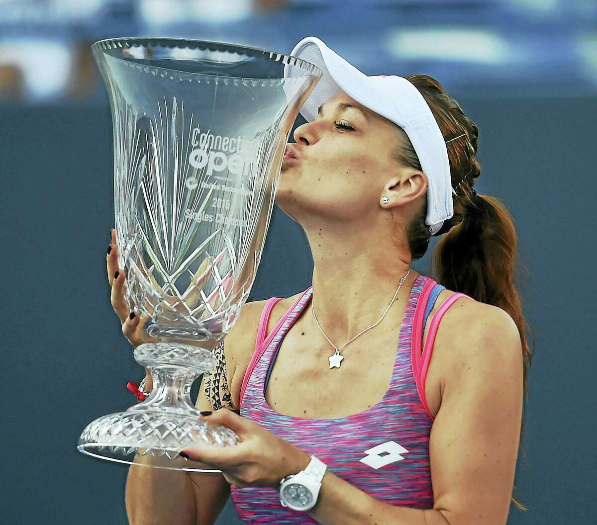 Agnieszka Radwanska kisses the trophy after defeating Elina Svitolina in the championship match at the Connecticut Open on Saturday.