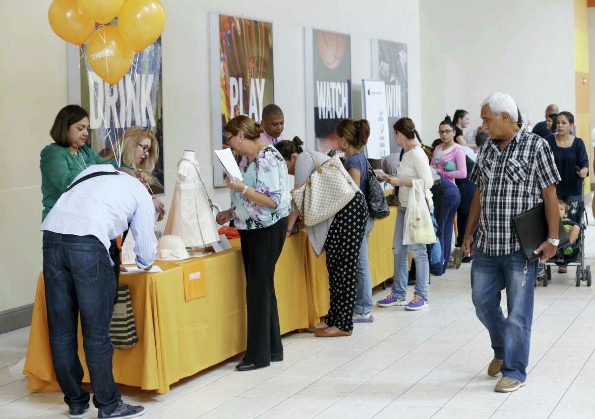 In this Tuesday, Oct. 6, 2015, file photo, job applicants fill out forms during a job fair at Dolphin Mall in Miami.