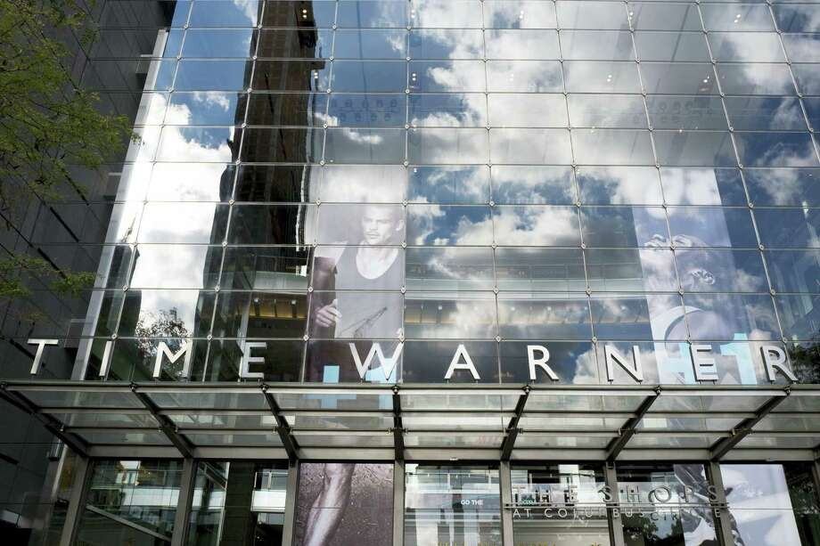 Clouds are reflected in the glass facade of the Time Warner building on Oct. 24, 2016 in New York. AT&T plans to buy Time Warner for $85.4 billion. Photo: AP Photo/Mark Lennihan  / Copyright 2016 The Associated Press. All rights reserved.