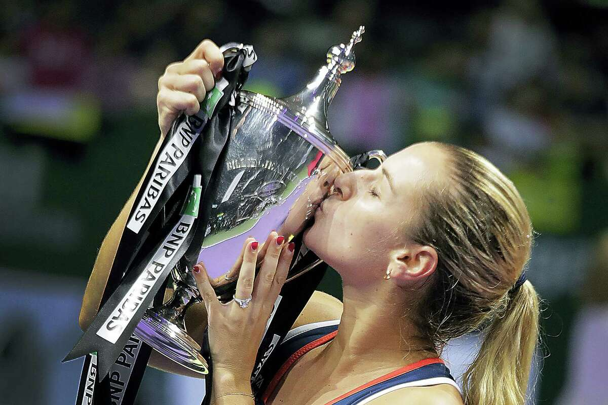 Dominika Cibulkova of Slovakia kisses her trophy after beating Angelique Kerber of Germany in their women's singles final match at the WTA tennis tournament in Singapore on Oct. 30, 2016.