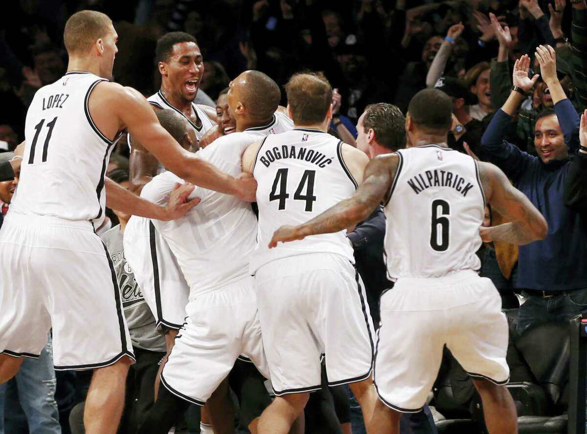 Brooklyn Nets players throng around Nets' guard Randy Foye, third from left, as they celebrate the Nets 120-118 win over the Charlotte Hornets Monday in Brooklyn. Foyle shot the winning three-pointer. Nets center Brook Lopez (11), Nets' guard Bojan Bogdanovic and Nets' guard Sean Kilpatrick (6) try to get in on the celebration.