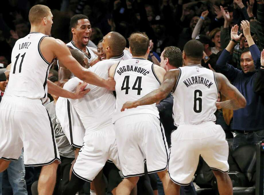 Brooklyn Nets players throng around Nets' guard Randy Foye, third from left, as they celebrate the Nets 120-118 win over the Charlotte Hornets Monday in Brooklyn. Foyle shot the winning three-pointer. Nets center Brook Lopez (11), Nets' guard Bojan Bogdanovic and Nets' guard Sean Kilpatrick (6) try to get in on the celebration. Photo: KATHY WILLENS - THE ASSOCIATED PRESS  / Copyright 2016 The Associated Press. All rights reserved.