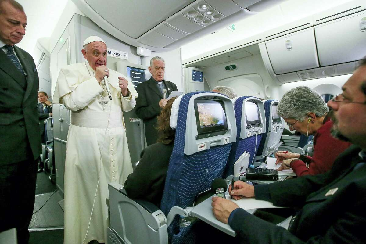 In this photo taken Feb. 17, 2016 Pope Francis meets journalists aboard the plane during the flight from Ciudad Juarez, Mexico to Rome, Italy. The pope has suggested that women threatened with the Zika virus could use artificial contraception but not abort their fetus, saying there's a clear moral difference between aborting a fetus and preventing a pregnancy.