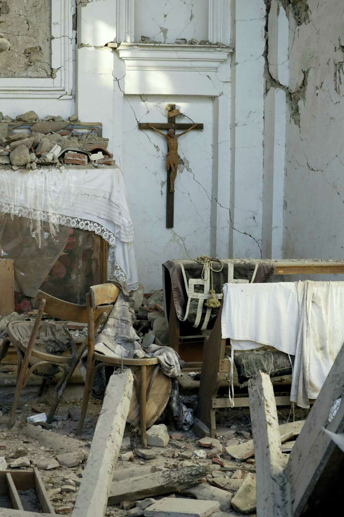 A crucifix hangs on the wall of the severely damaged church in the village of Santi Lorenzo e Flaviano, central Italy, Saturday, Aug. 27, 2016. Italians bid farewell Saturday to victims of the devastating earthquake that struck a mountainous region of central Italy this week.