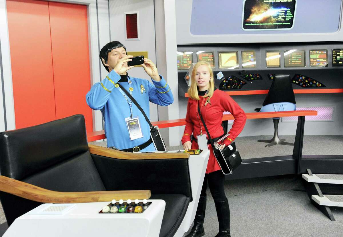 "Keith Schubert, left, of Peru, N.Y., dressed as Mr. Spock, and his daughter Tiffany, right, dressed as a crew member, take photographs during a tour of the replica starship Enterprise from the original ""Star Trek"" series during the Trekonderoga festival in Ticonderoga, N.Y."