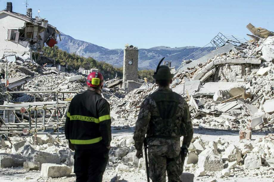 A firefighter, left, and an alpine soldier look at rubble in the hilltop town of Amatrice as an earthquake with a preliminary magnitude of 6.6 struck central Italy on Oct. 30, 2016. A powerful earthquake rocked the same area of central and southern Italy hit by quake in August and a pair of aftershocks last week, sending already quake-damaged buildings crumbling after a week of temblors that have left thousands homeless. Photo: Massimo Percossi/ANSA Via AP  / ANSA