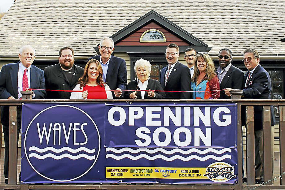 A grand opening was held for WAVES, a nautical-themed American fare restaurant, in East Hampton Oct. 24. Larry McHugh, president of the Middlesex County Chamber of Commerce, joined owner Paul Angelico with staff and local officials, including East Hampton Town Manager Michael Maniscalco, Councilors Peter Brown, Melissa Engel and Kevin Reich and state Sen. Art Linares. Nikki O'Neill, wife of late Gov. William A. O'Neill, cut the ribbon. The O'Neill family once owned a bar at the building when it was known as O'Neill Taproom. Photo: Contributed Photo