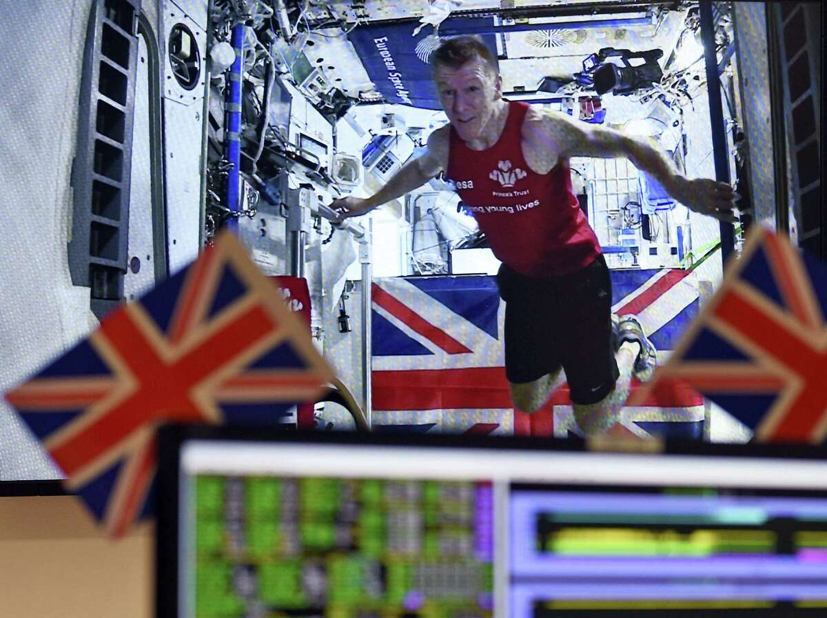 The Associated Press British astronaut Tim Peake is seen on a video screen transmitted from the International Space Station Sunday. Peake ran a 26.2-mile marathon on a tread mill in space while the London Marathon took place in England.