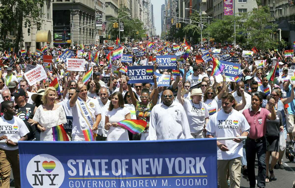 New York Gov. Andrew M. Cuomo, third left, waves as he leads a large group while he walks in the New York City Pride Parade Sunday, June 26, 2016 in New York City.