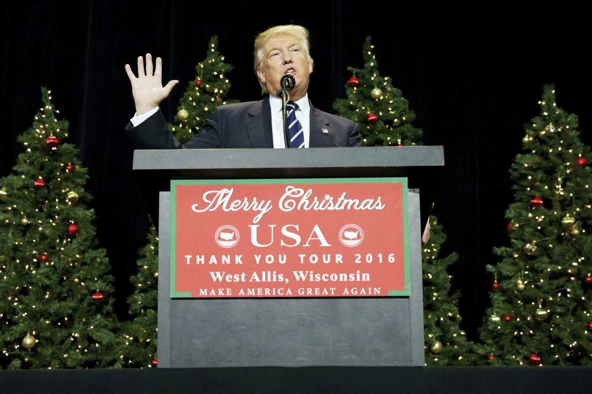 In this Dec. 13, 2016 photo, President-elect Donald Trump speaks during a rally at the Wisconsin State Fair Exposition Center in West Allis, Wis. Trump is embracing some of his top attacks on Hillary Clinton as he forms his new administration, engaging in some of the same behavior he used against his rival during the presidential campaign.