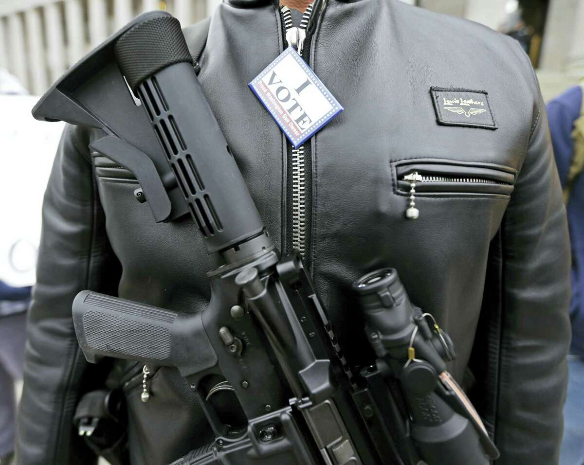 """In this Jan. 15, 2015 photo, Mark Ramirez of Bainbridge Island, Wash., wears his Colt M4 gun and a button that reads """"I Vote — a Proud Washington Gun Owner,"""" during a gun rights rally at the Capitol in Olympia, Wash. Washington is one of four states putting initiatives before voters in the 2016 election that would broaden background checks or restrict who can buy guns and ammunition."""