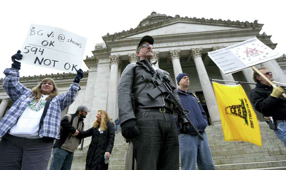 In this Jan. 15, 2015 photo, Mark Ramirez, center, of Bainbridge Island, Wash., wearing his Colt M4 gun, and others participate in a gun-rights rally at the Capitol in Olympia, Wash. Washington is one of four states putting initiatives before voters in the 2016 election that would broaden background checks or restrict who can buy guns and ammunition.