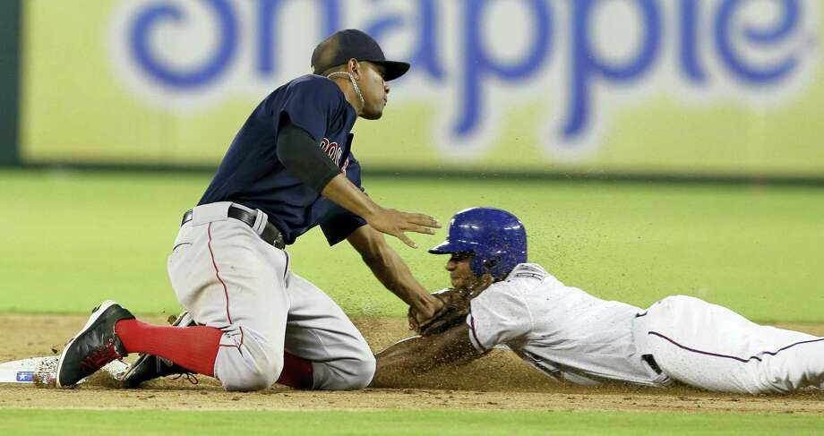 Elvis Andrus, right, is caught stealing second base as Red Sox shortstop Xander Bogaerts applies the tag in the fourth inning on Friday. Photo: LM Otero — The Associated Press  / Copyright 2016 The Associated Press. All rights reserved. This material may not be published, broadcast, rewritten or redistribu