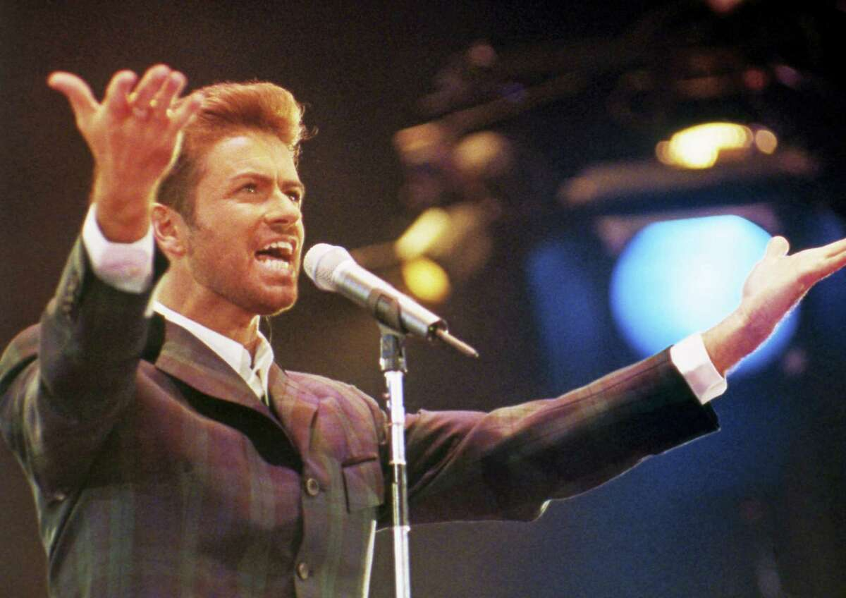 """In this Dec. 2, 1993 file photo, George Michael performs at """"Concert of Hope"""" to mark World AIDS Day at London's Wembley Arena. According to a publicist on Sunday, Dec. 25, 2016, the singer has died at the age of 53. PHOTO BY Gill Allen - AP Photo"""