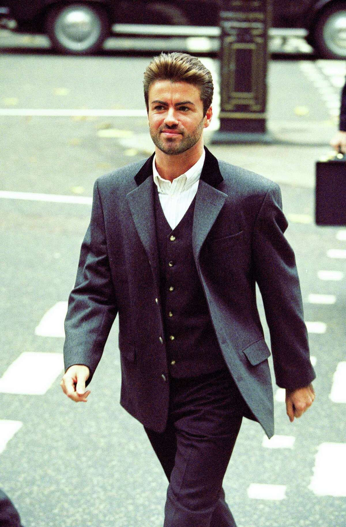 In this Oct. 28, 1993, file photo, pop star George Michael arrives to give evidence at the Royal Courts of Justice in London. Michael was petitioning the court to release him from his contract with Sony Music Entertainment (UK) Ltd. Michael, who rocketed to stardom with WHAM! and went on to enjoy a long and celebrated solo career lined with controversies, has died, his publicist said Sunday, Dec. 25, 2016. He was 53. PHOTO BY Alistair Grant - AP Photo