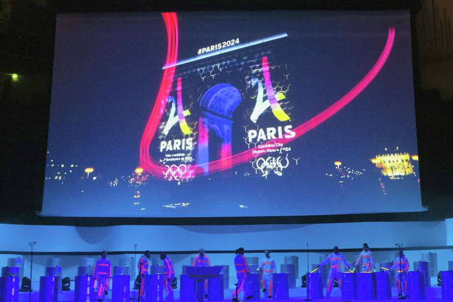 Dancers perform on stage as the Eiffel Tower-shaped bid logo for the Paris 2024 is projected on the Arc de Triomphe on a giant screen during the official presentation of Paris as candidate for the 2024 Olympic summer games in Paris, France, Wednesday, Feb. 17, 2016. Paris, which hosted the Olympics in 1900 and 1924, is competing against Budapest, Rome and Los Angeles for the games. The International Olympic Committee will choose the host city in September 2017. Photo: AP Photo/Francois Mori   / AP
