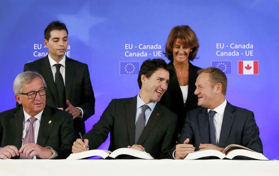 Canadian Prime Minister Justin Trudeau, center front, sits with European Commission President Jean-Claude Juncker, left, and European Council President Donald Tusk, right, as they sign the Comprehensive Economic and Trade Agreement (CETA) during an EU-Canada summit at the European Council building in Brussels on Oct. 30, 2016. Photo: Francois Lenoir/Pool Photo Via AP  / Reuters Pool