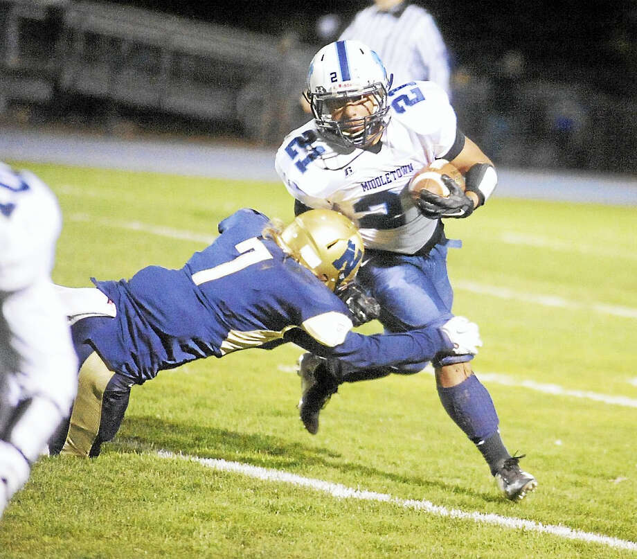 Middletown senior Ibn Lombardo looks to break a tackle against Newington on Friday night. Photo: Jimmy Zanor -The Middletown Press