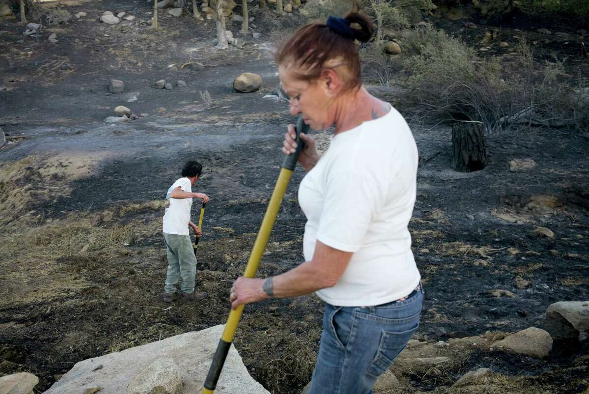 Rick Gutierrez and wife, Jean, foreground, put out hotspots on their neighbor's property near Mountain Mesa, Calif. The couple said they evacuated last night but came back shortly after midnight to keep an eye on their home.