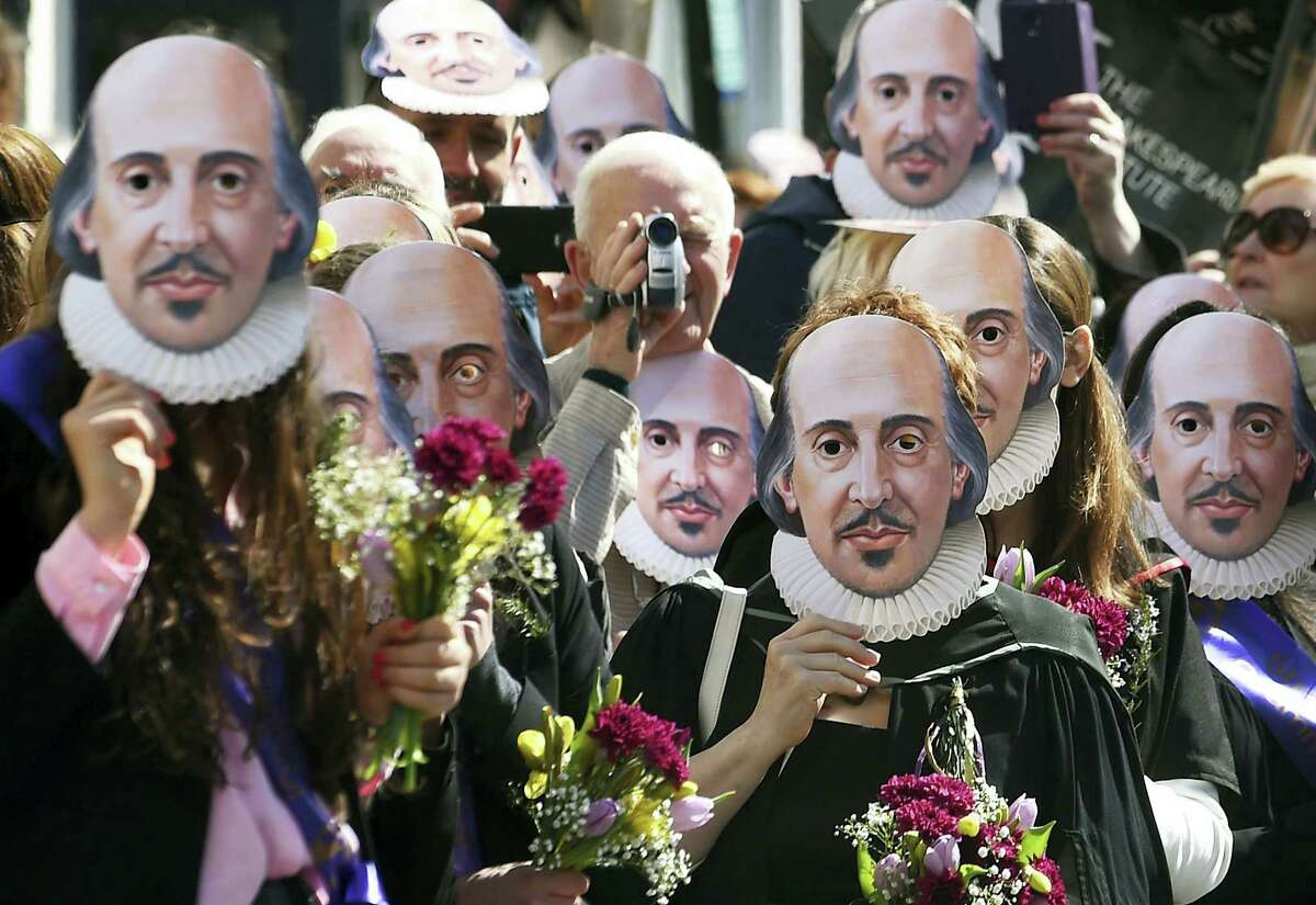 Members of the public wear William Shakespeare masks during a parade marking 400 years since the death of the playwright in Stratford-upon-Avon, England, Saturday, April 23, 2016. The legacy of Shakespeare, who is buried in Stratford's Holy Trinity Church, will be brought to life by a host of actors, dancers and theatrical extras, including local schoolchildren and the public, who are gathering to mark the anniversary of the Bard's death.