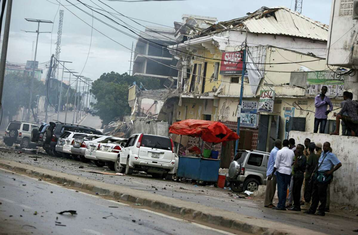 Security forces examine the scene after a bomb attack on Nasahablod Hotel in Mogadishu, Somalia, Saturday, June 25, 2016. A Somali police officer says a suicide car bomber detonated an explosives-laden vehicle at the gate of a hotel in Mogadishu followed by gunmen who were fighting their way into the hotel.