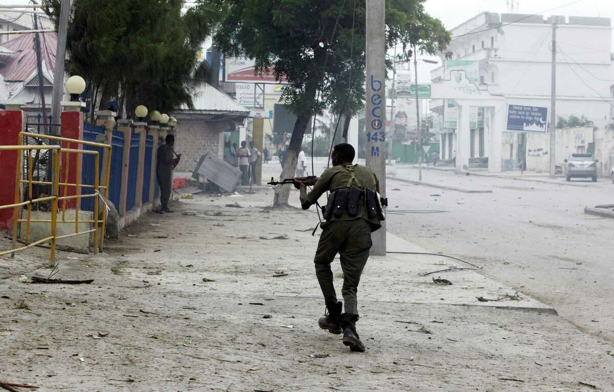 A Somali soldier takes position during an attack on Nasahablod Hotel, in Mogadishu, Somalia, Saturday, a June 25, 2016 . A Somali police officer says a suicide car bomber detonated an explosives-laden vehicle at the gate of a hotel in Mogadishu followed by gunmen who were fighting their way into the hotel.