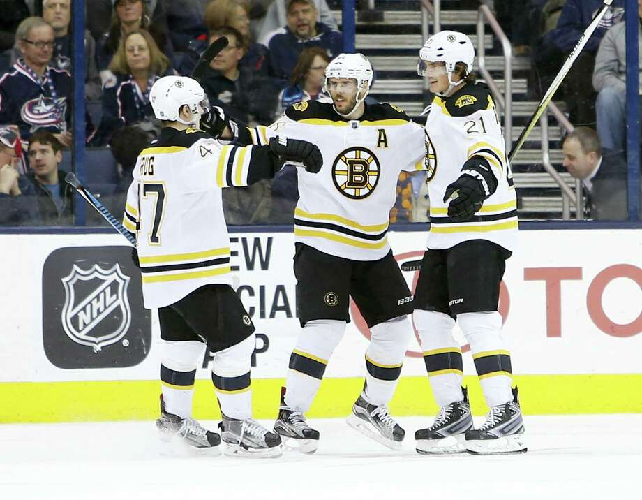 Boston Bruins' Loui Eriksson, right, of Sweden, celebrates his game-winning goal against the Columbus Blue Jackets with teammates Torey Krug, left, and David Krejci, of the Czech Republic, during the overtime period of an NHL hockey game Tuesday, Feb. 16, 2016, in Columbus, Ohio. The Bruins beat the Blue Jackets 2-1 in overtime. (AP Photo/Jay LaPrete) Photo: AP / FR52593 AP